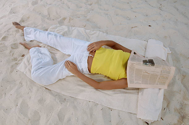 woman sleeping on beach - newspaper beach stockfoto's en -beelden