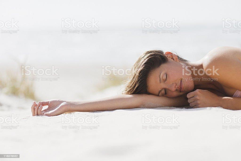 Mulher dormindo na praia - foto de acervo