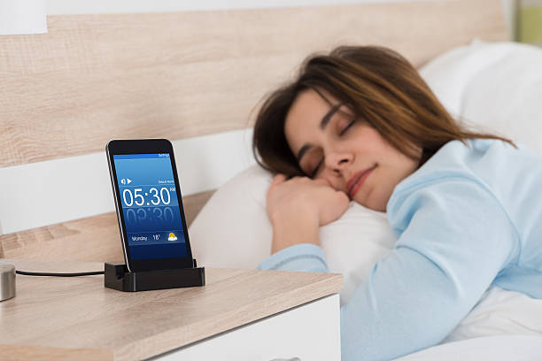 woman sleeping on bed with alarm on mobile phone - alarm clock stock photos and pictures