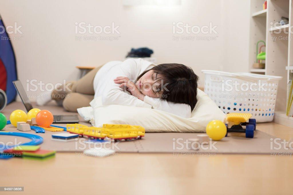 Femme allongée sur le sol plein de jouet - Photo