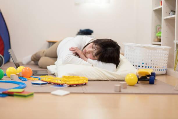 Woman sleeping on floor full of toy stock photo
