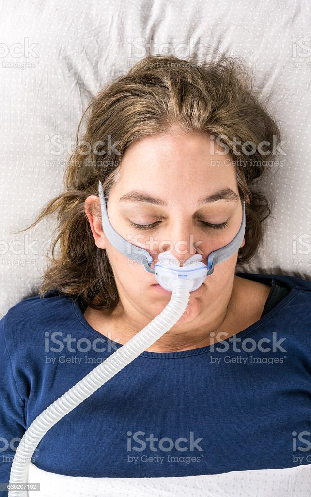 Woman sleeping on her back with CPAP, sleep apnea treatment. stock photo