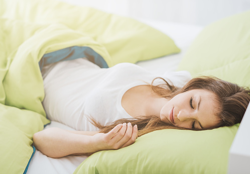 Smiling young woman sleeping in her bed in the late morning, healthy lifestyle and relax concept