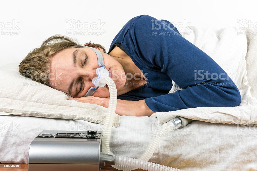 Woman sleeping on her side with CPAP machine. stock photo