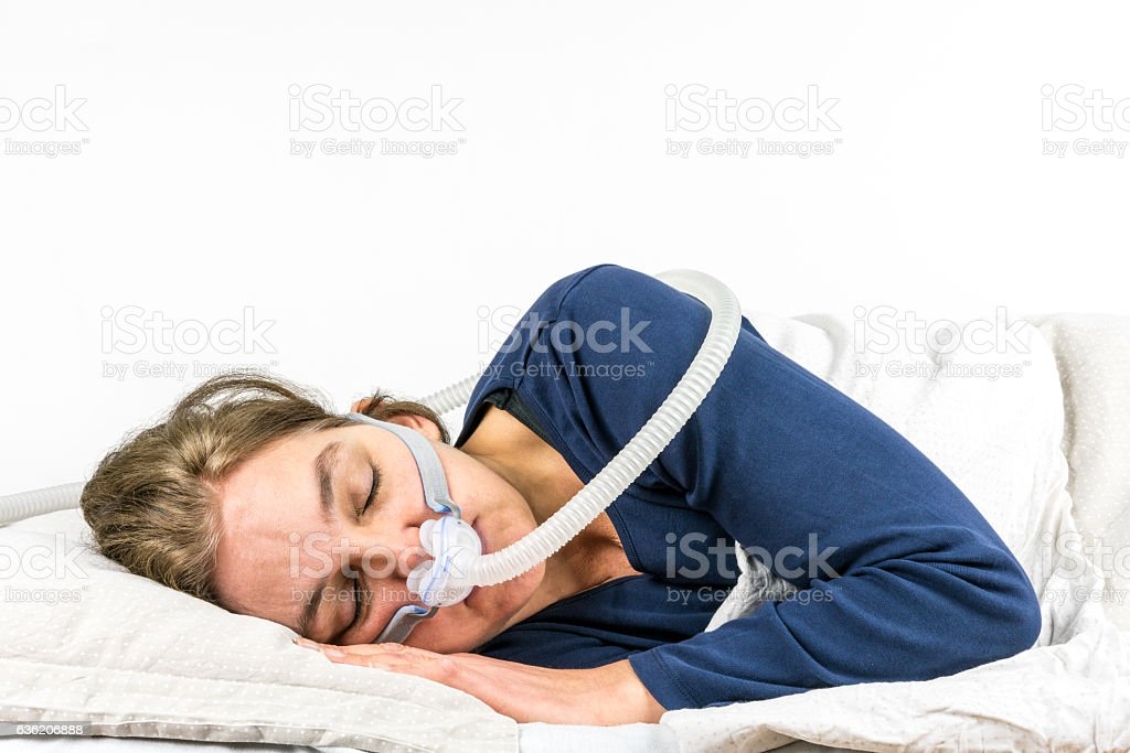 Woman sleeping on her side with CPAP, sleep apnea treatment. stock photo