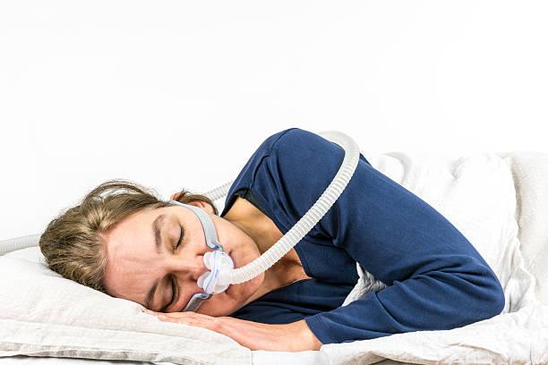 Woman sleeping on her side with CPAP, sleep apnea treatment. stock photo