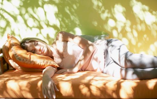Woman sleeping on sunny patio bench