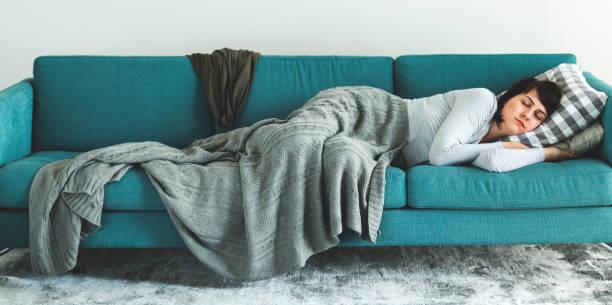 femme endormie sur le canapé-lit - faire un somme photos et images de collection