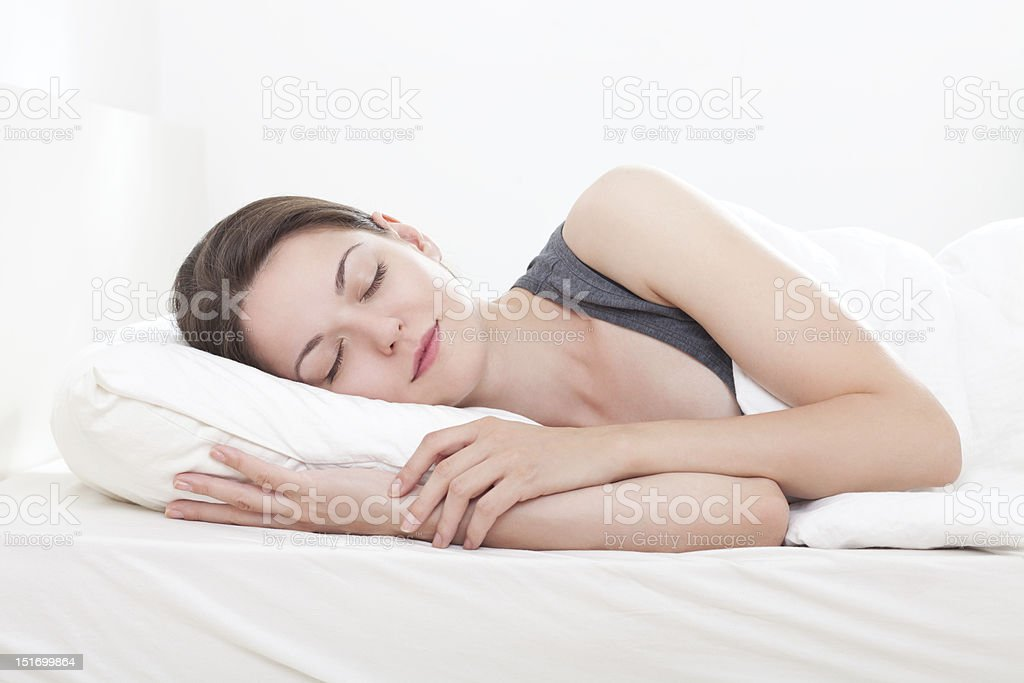Woman sleeping peacefully on a white bed stock photo