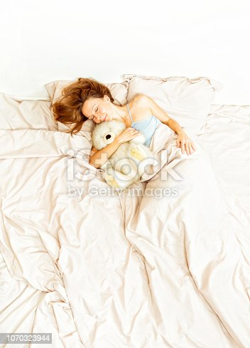 Woman sleeping in bed with teddy
