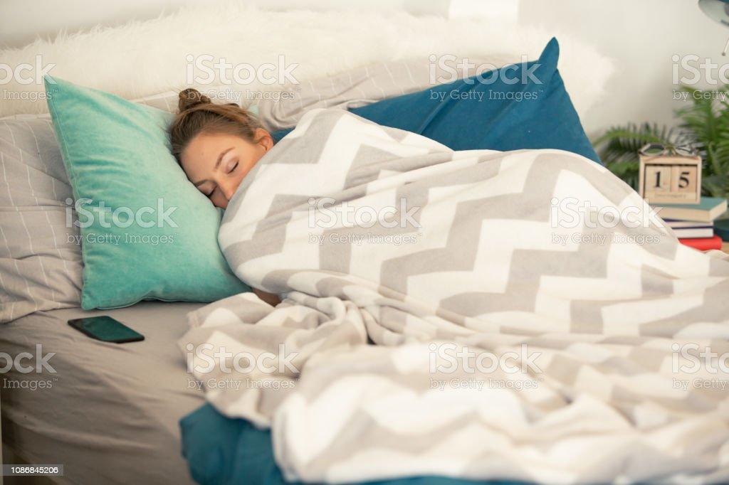 Woman sleeping tucked in a warm blanket stock photo