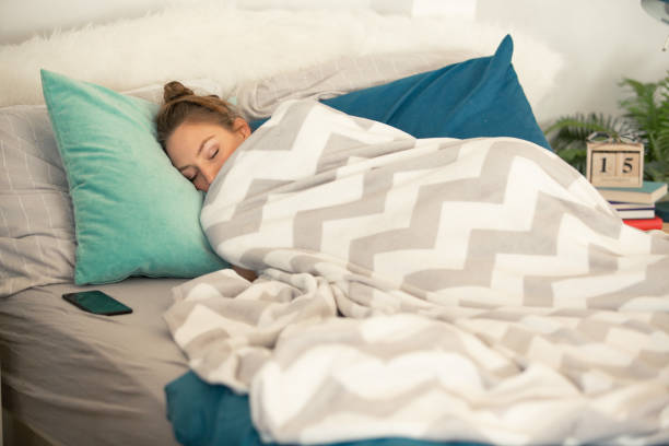 Woman sleeping tucked in a warm blanket Young woman is sleeping in her cozy bed, covered with warm blanket. Her smart phone is near her. wrapped in a blanket stock pictures, royalty-free photos & images