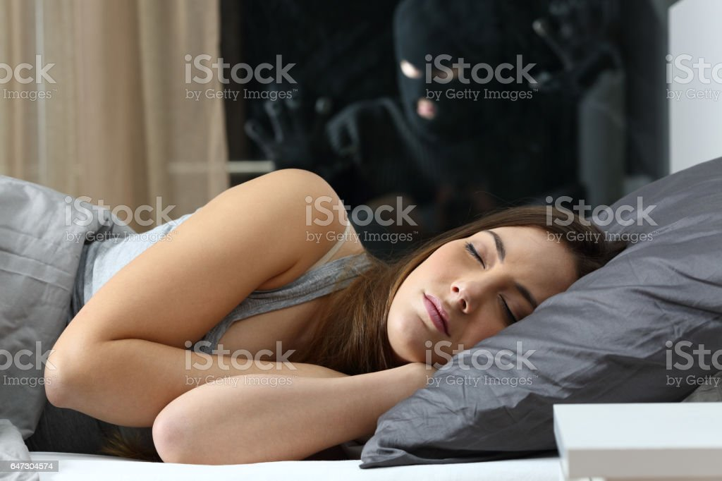 Woman sleeping with an intruder watching stock photo