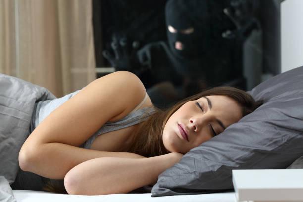 frau schläft mit einem eindringling beobachten - jagdthema schlafzimmer stock-fotos und bilder