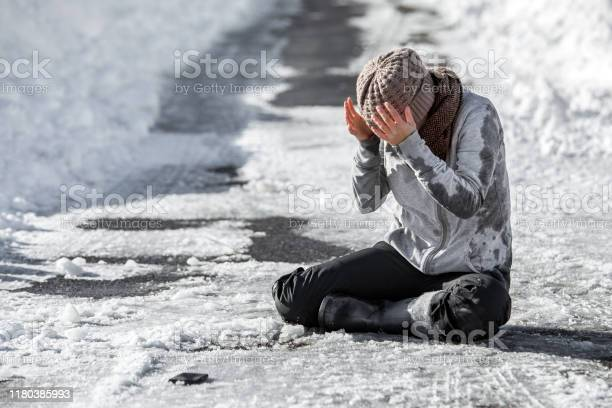 Photo of Woman slipped on the winter road, accident and injury, black ice and danger, copyspace