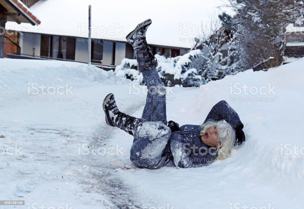 Une femme a glissé sur la route d'hiver, est tombé vers le bas et se blesse photo libre de droits