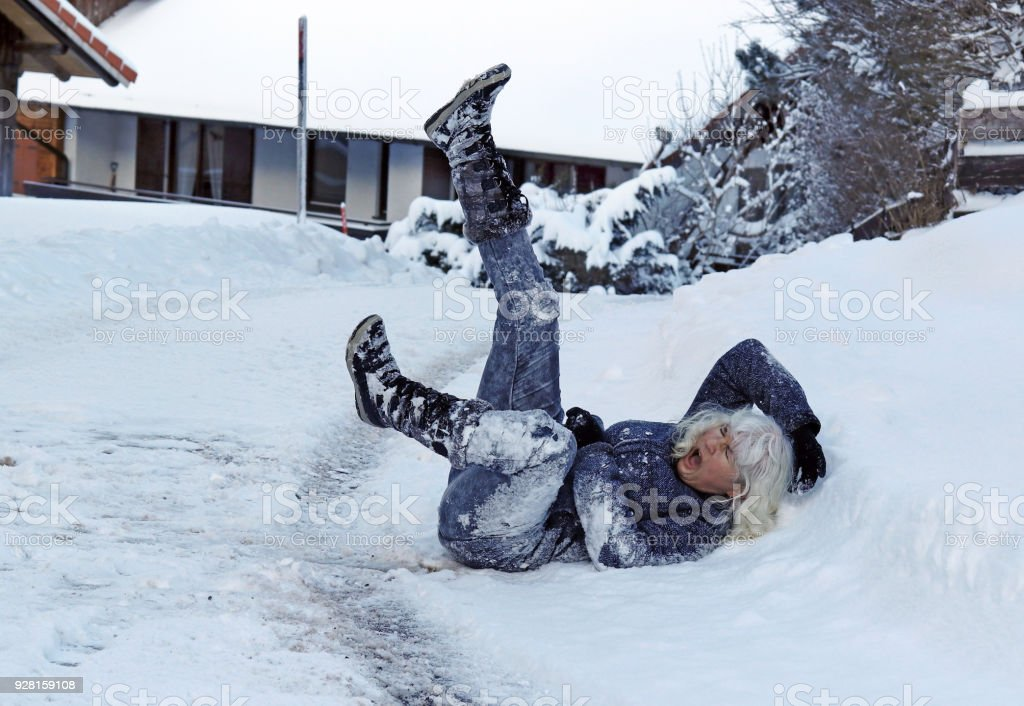 A woman slipped on the winter road, fell down and hurt herself stock photo