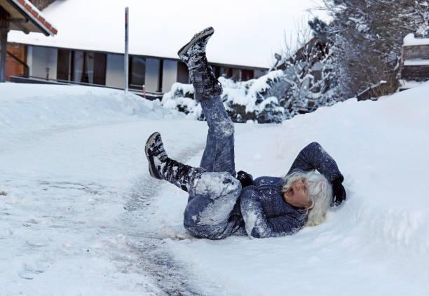 en kvinna som halkade på vägen vinter, föll ner och skada sig själv - cold street bildbanksfoton och bilder