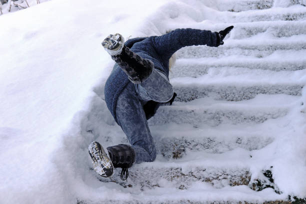 a woman slips and fell on a wintry staircase - spadać zdjęcia i obrazy z banku zdjęć