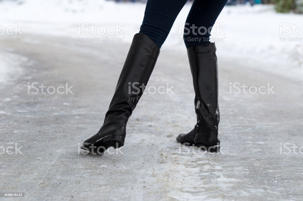 Woman slips on slippery road covered with ice. Concept of injury risk in winter. stock photo