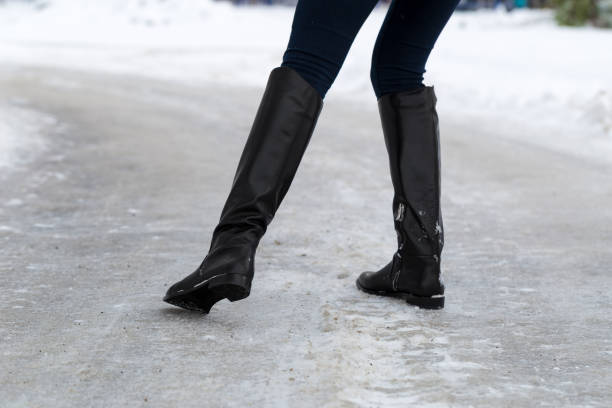 Woman slips on slippery road covered with ice. Concept of injury risk in winter. Woman slips on slippery road covered with ice. Concept of injury risk in winter. Close shot. slippery stock pictures, royalty-free photos & images