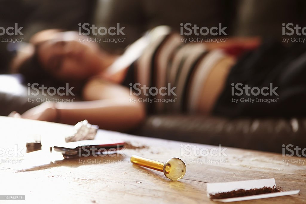 Woman Slumped On Sofa With Drug Paraphernalia In Foreground stock photo