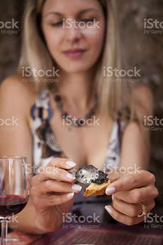 Woman smearing bread with black tapenade. stock photo