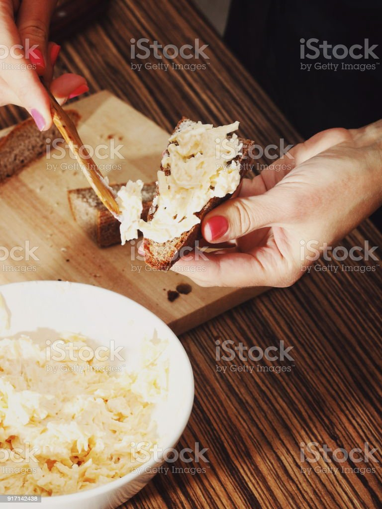 Woman Smears on Dark Bread Cheese with garlic stock photo