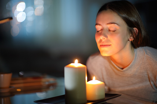 Woman smelling a lighted candle in the night