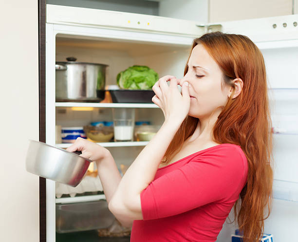 Woman smelling disgusting food and holding her nose young woman in red  holding her nose because of bad smell from food near refrigerator  at home addle stock pictures, royalty-free photos & images