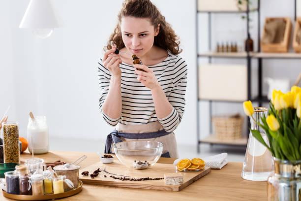 vrouw ruikende etherische olie - oil kitchen stockfoto's en -beelden