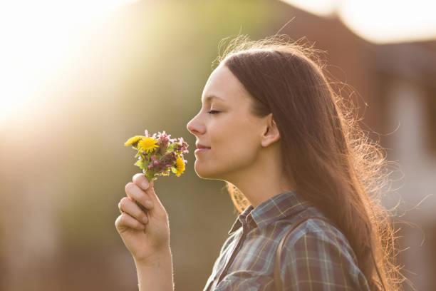 Frau, die duftenden Wiesenblumen im park – Foto