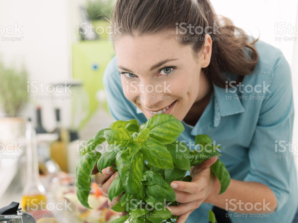 Woman smelling fresh basil at home stock photo
