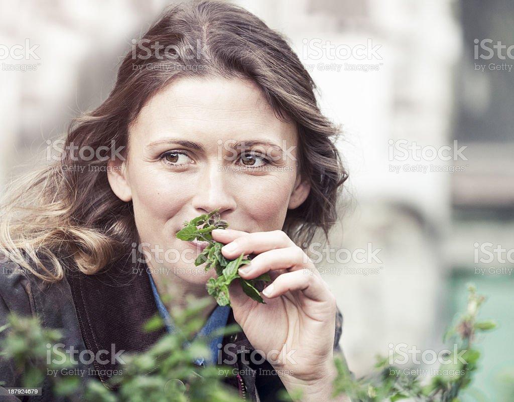 Woman smelling fresh herbs stock photo
