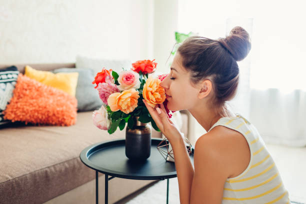 woman smelling fresh roses in vase on table. housewife taking care of coziness in apartment. interior and decor - annusare foto e immagini stock