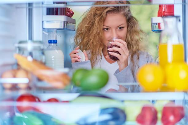 kvinna att lukta sylt framför kyl full av matvaror. - food woman to smell bildbanksfoton och bilder