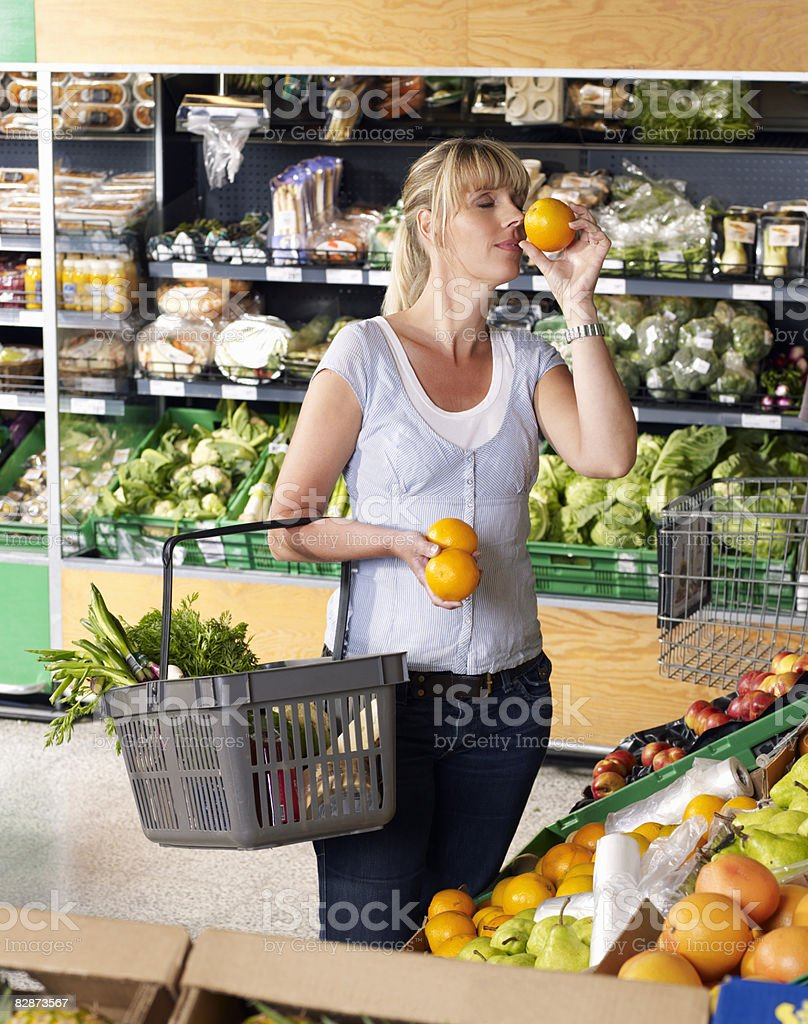Woman smelling oranges in supermarket royaltyfri bildbanksbilder