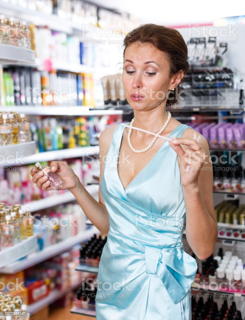 Stylish woman smelling perfume testers, choosing perfume in cosmetic...