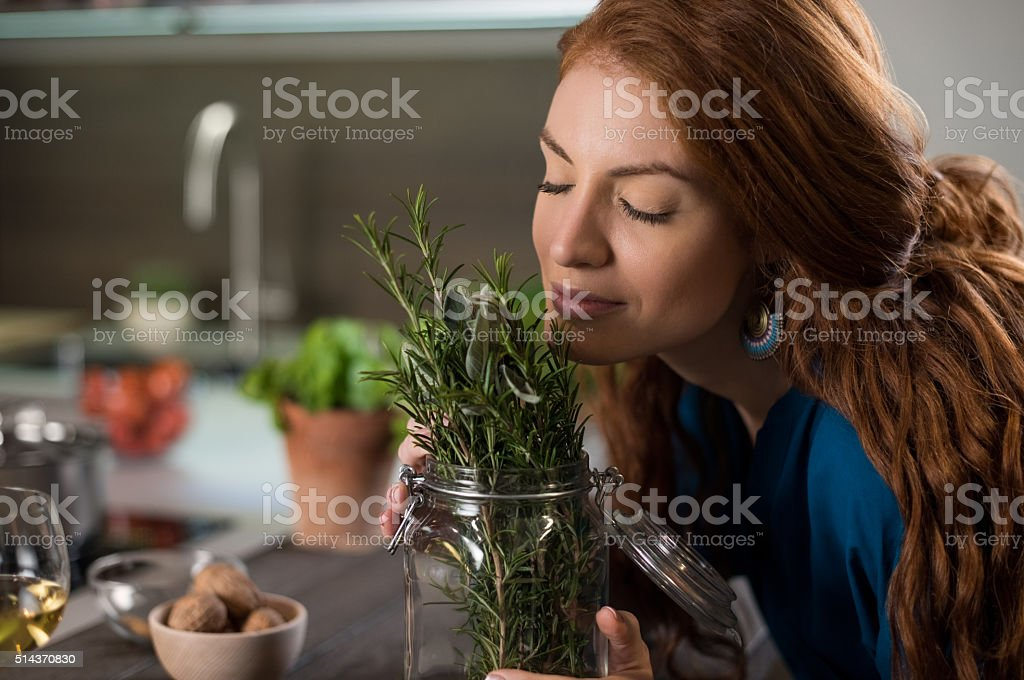 Woman smelling rosemary stock photo