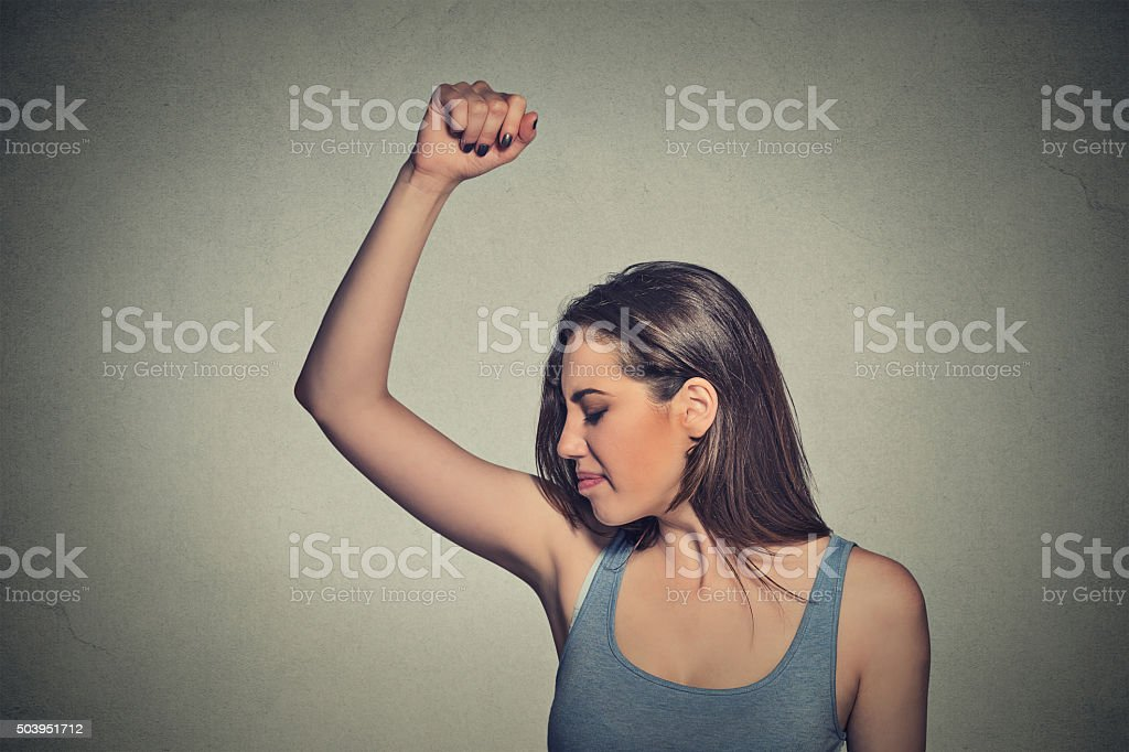 woman, smelling sniffing her wet armpit something stinks stock photo