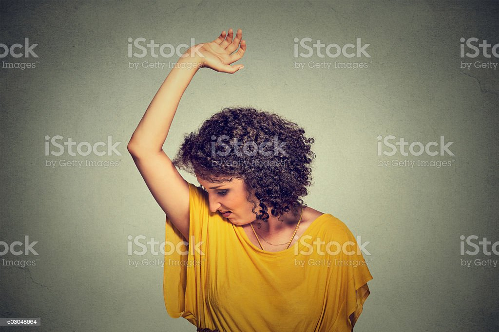 woman, smelling, sniffing her wet armpit, stinks bad odor stock photo