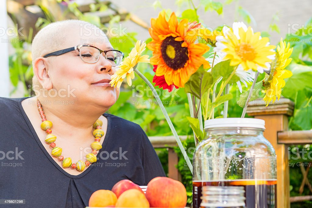 Woman Smells Scented Fresh Cut Flowers stock photo