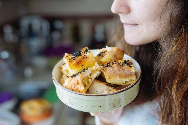 frau riecht türkische patty, börek - spieltag vorspeisen stock-fotos und bilder