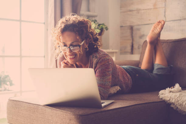 Woman smile and use an internet laptop connected to watch a movie or work easy at home in alternative office and lifestyle concept - freelance and free people with technology stock photo