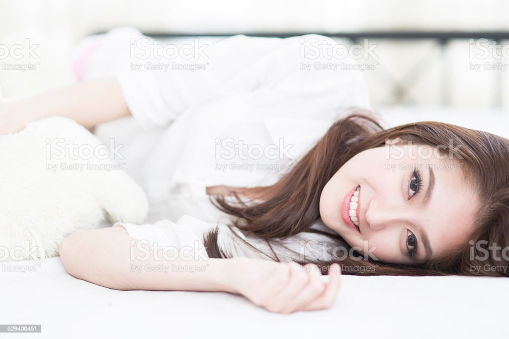 woman smile face close up while lying on the bed stock photo