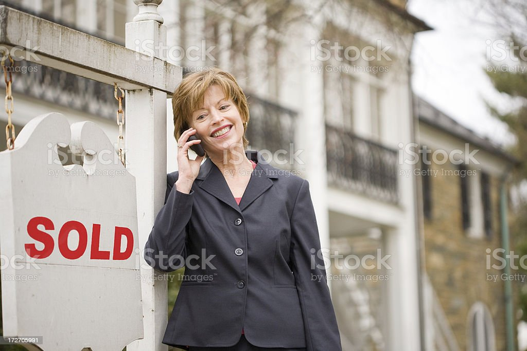 woman smiles in front of sold sign royalty-free stock photo