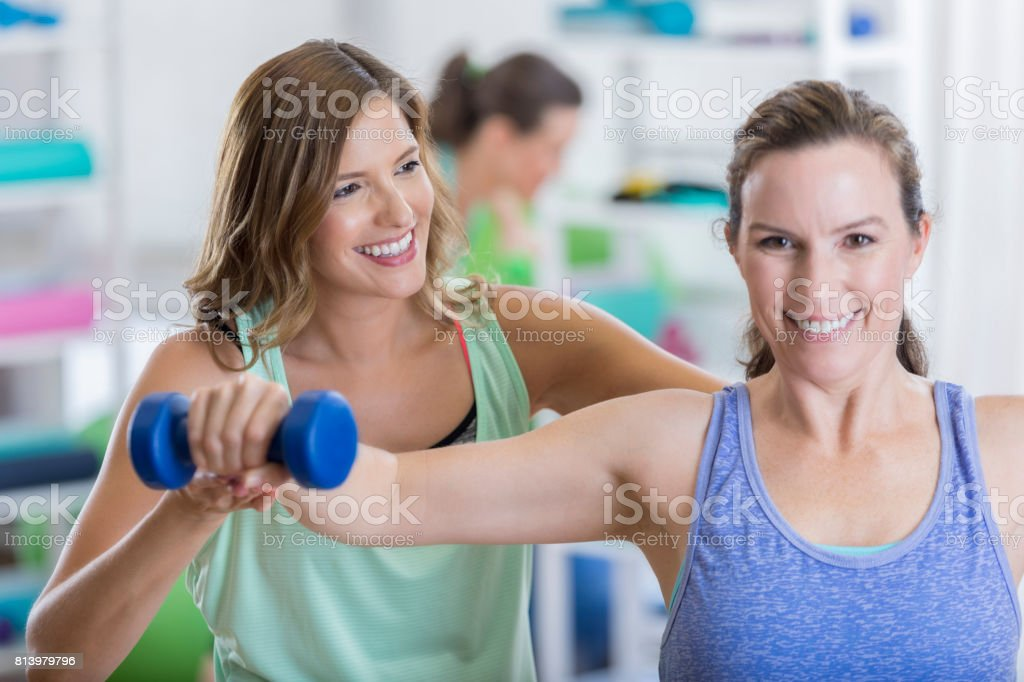 An attractive woman and her fitness instructor smile as the woman...