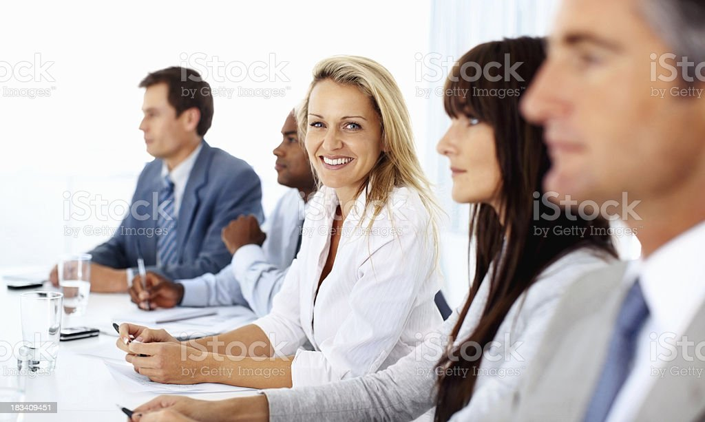 Woman smiling and looking at you during business meeting royalty-free stock photo