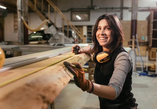 Woman smiling and measuring wooden board in a carpentry woorkshop stock photo