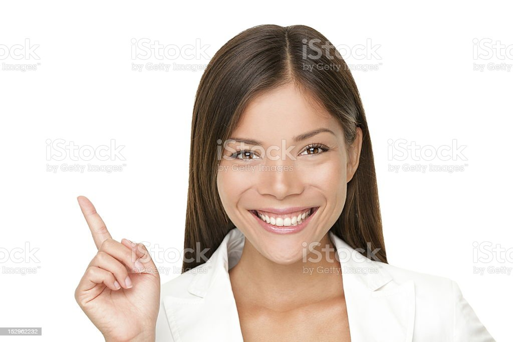 A woman smiling and pointing upwards stock photo